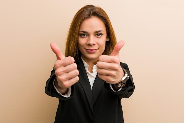 A mulher de negócio caucasiano nova com polegares levanta, felicidades sobre algo, apoia e respeita o conceito.