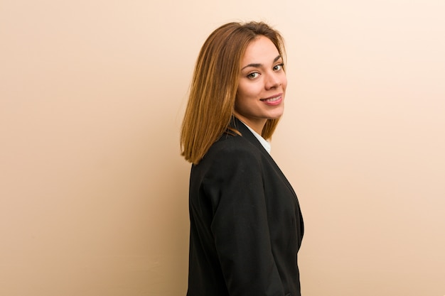 A mulher de negócio caucasiano nova olha de lado sorrindo, alegre e agradável.