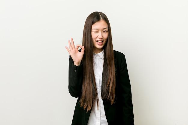 A mulher de negócio consideravelmente chinesa nova pisca um olho e prende um gesto aprovado com a mão.