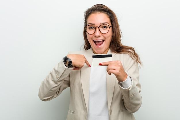 A mulher de negócio européia nova que guarda um cartão de crédito surpreendeu apontar-se, sorrindo amplamente.