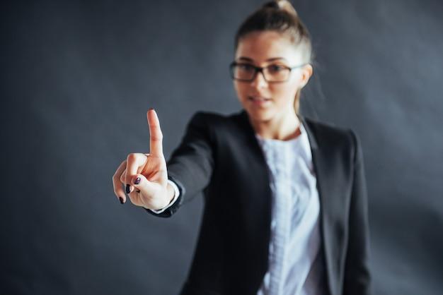 A mulher de negócio feliz aparece o dedo, estando em um preto no, amigável, sorrindo, foco na mão.