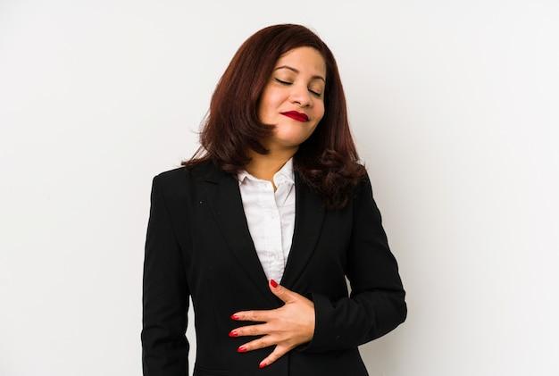 A mulher de negócio latin da idade média isolada toca na barriga, sorri delicadamente, comendo e conceito da satisfação.