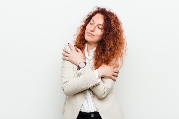 A mulher de negócio natural nova do ruivo abraça, sorrindo despreocupado e feliz.