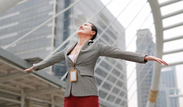 A mulher de negócio nova bonita que sente livre com os braços largos abre fora.