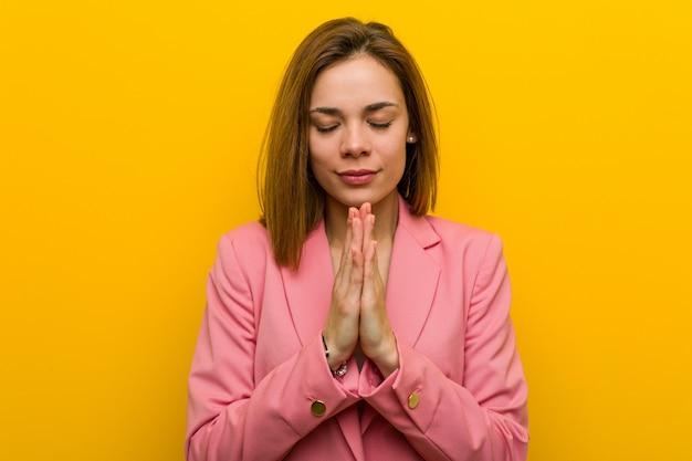 A mulher de negócio nova da forma que guarda as mãos dentro reza perto da boca, sente segura.