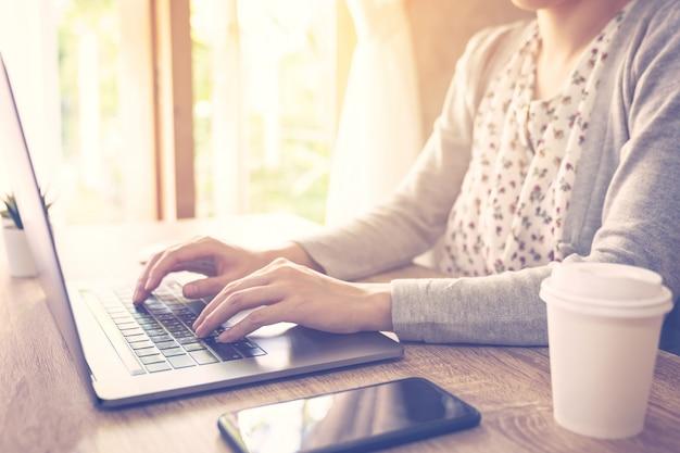 A mulher de negócio que usa o laptop faz a atividade em linha no escritório de madeira da tabela no escritório home.