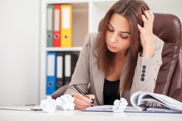 A mulher de negócios aborrecida nova que senta-se na tabela com portátil e quer dormir quando bocejo no local de trabalho no escritório moderno.