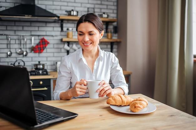 A mulher de negócios alegre agradável senta-se na tabela na cozinha e olha-o portátil. ela trabalha em casa. modelo segurar copo branco com bebida e sorriso.
