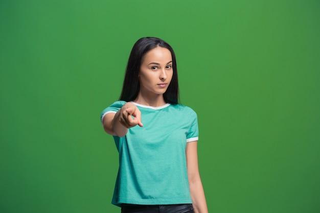 A mulher de negócios arrogante apontar e querer você, retrato de closeup de metade do comprimento sobre fundo verde.