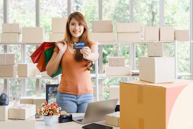 A mulher de negócios asiática feliz bonita jovem com carinha está mostrando o cartão de crédito ou cartão de débito