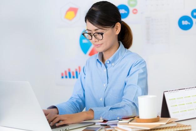 A mulher de negócios asiática relaxa ao trabalhar conceitos do negócio e da finança.