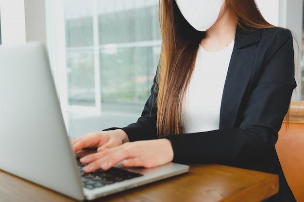 A mulher de negócios asiáticos do close up que usa o portátil da tecnologia com máscara protetora médica da segurança para impede o coronavirus.
