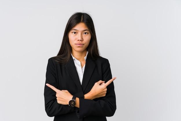 A mulher de negócios asiáticos jovens aponta lateralmente, está tentando escolher entre duas opções.
