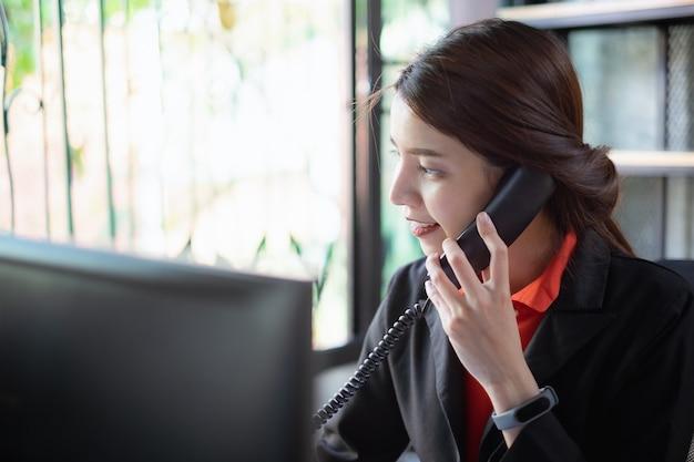A mulher de negócios bonita discute com o sócio pelo telefone no escritório.
