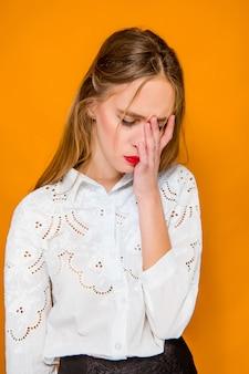 A mulher de negócios bonita jovem frustrada grave em fundo laranja