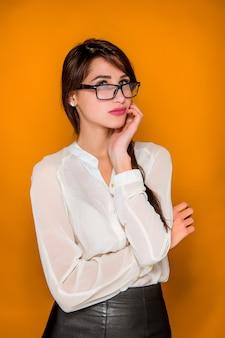 A mulher de negócios bonita jovem frustrada grave na parede laranja