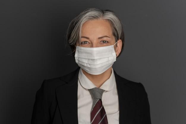 A mulher de negócios consideravelmente caucasiano que veste a máscara protetora e o formalwear sorri no fundo cinzento. copie espaço nos dois lados. feche o retrato. conceito de surto de coronavírus