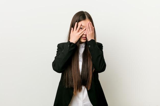 A mulher de negócios consideravelmente chinesa nova pisca através dos dedos assustada e nervosa.