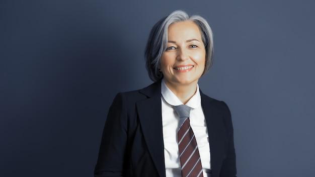 A mulher de negócios de meia idade positiva sem máscara sorri alegremente. mulher grisalha otimista vestindo formalwear posando em fundo cinza azul. espaço de texto ou cópia nos dois lados. foto de estúdio. imagem enfraquecida