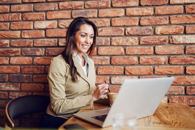 A mulher de negócios de sorriso focalizada vestiu o assento ocasional esperto no café, mexendo o café e olhando o portátil.