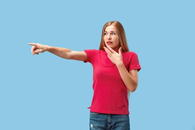 A mulher de negócios feliz aponta e quer você, retrato de meio comprimento closeup na parede azul