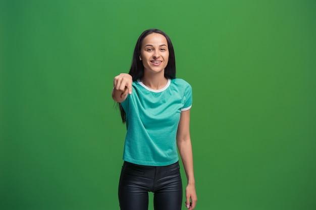 A mulher de negócios feliz aponta você e quer você, retrato de closeup de metade do comprimento sobre fundo verde.