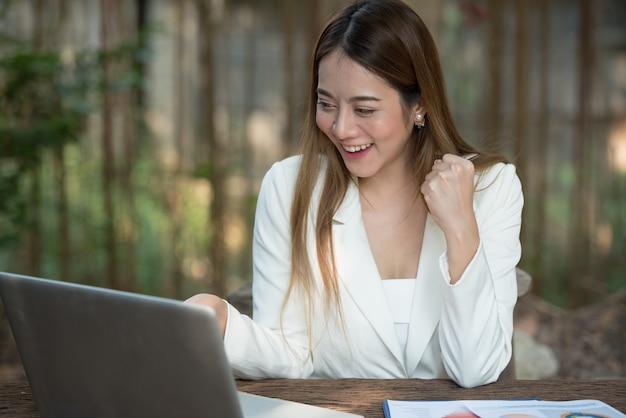 A mulher de negócios feliz aprecia com sorriso e riso do trabalho no laptop, fim acima.