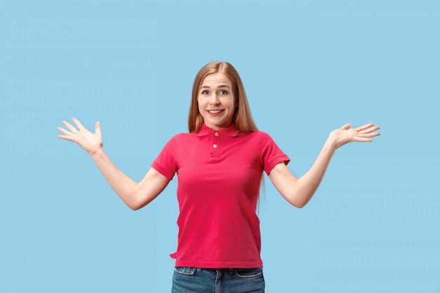 A mulher de negócios feliz em pé e sorrindo contra a parede azul