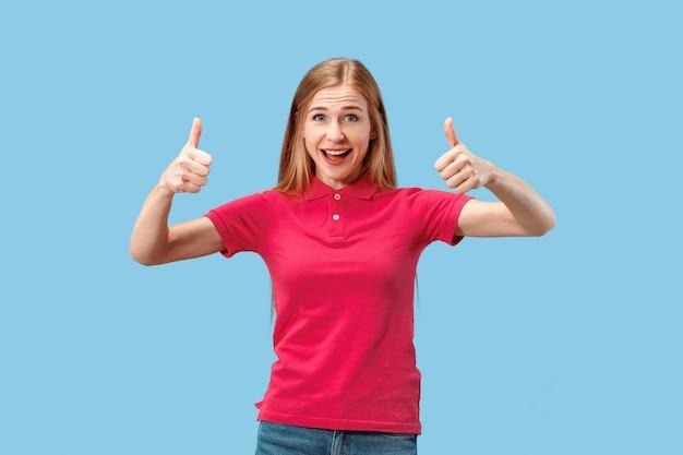 A mulher de negócios feliz em pé e sorrindo contra o espaço azul.