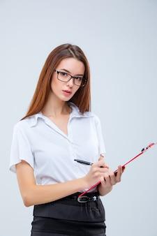A mulher de negócios jovem com caneta e tablet para anotações na parede cinza