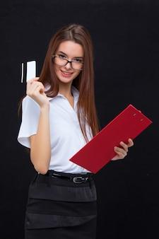 A mulher de negócios jovem com cartão de crédito e tablet para anotações na parede cinza