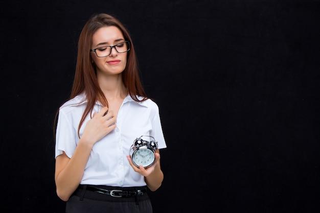 A mulher de negócios jovem com despertador na parede preta