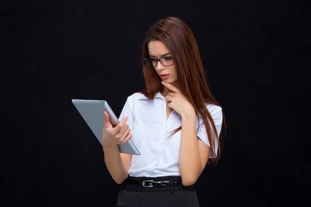 A mulher de negócios jovem com tablet na parede preta