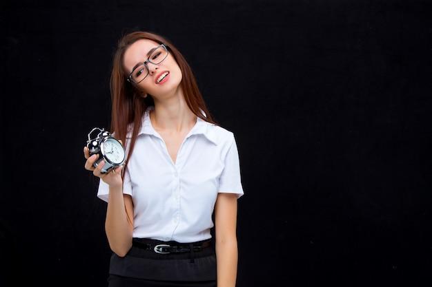 A mulher de negócios jovem em copos com despertador em um espaço preto