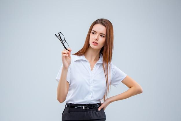 A mulher de negócios jovem em fundo cinza