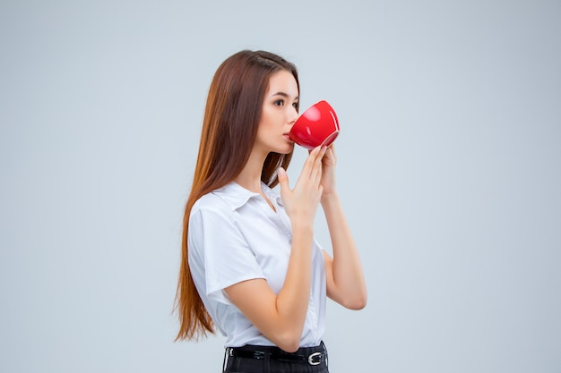 A mulher de negócios jovem eu com uma xícara de café vermelha em um espaço cinza