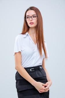 A mulher de negócios jovem na parede cinza