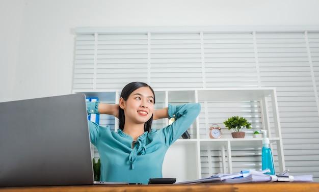 A mulher de negócios jovem que trabalha em casa levanta suas mãos sobre a cabeça para relaxar do trabalho duro, coronavírus.