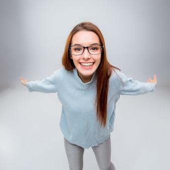A mulher de negócios jovem sorridente em fundo cinza