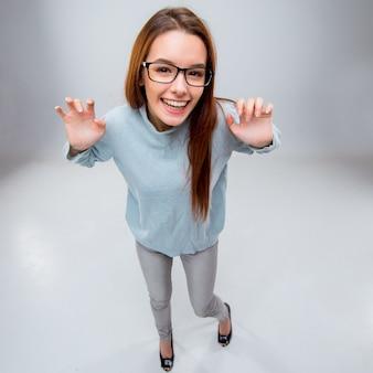 A mulher de negócios jovem sorridente na parede cinza