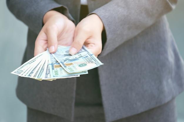 A mulher de negócios mantém o dinheiro e dá o dinheiro do dólar. concentre-se no dólar.