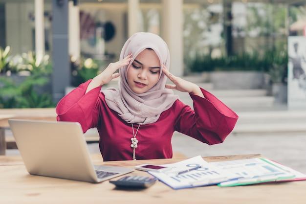 A mulher de negócios muçulmano asiática seriamente tem uma dor de cabeça.