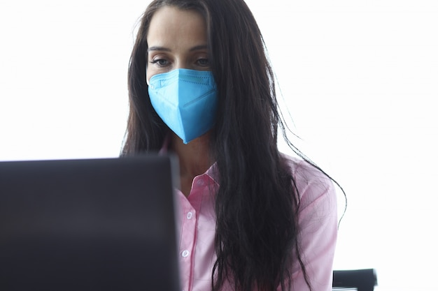A mulher de negócios na máscara azul usa o retrato do portátil.
