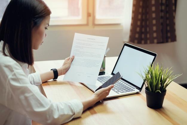 A mulher de negócios no escritório e usa o computador para executar a contabilidade financeira.