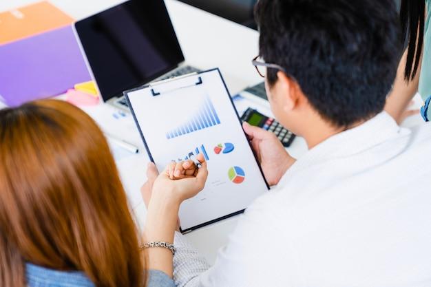 A mulher de negócios nova explica o detalhe do plano de marketing na folha de dados para team com o portátil na tabela.