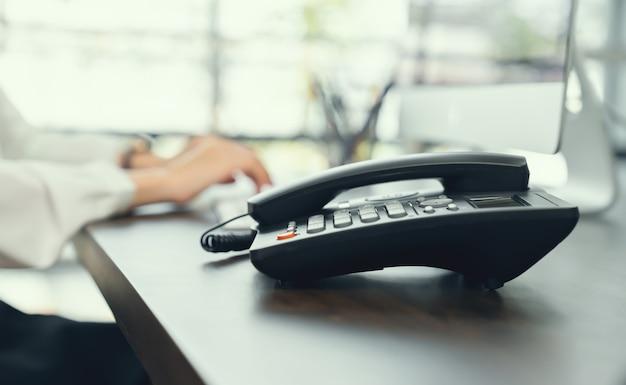 A mulher de negócios que trabalha no computador e o escritório telefonam na mesa.