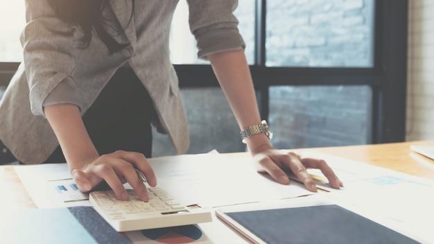 A mulher de negócios que usa a calculadora e o portátil para faz a matemática financia na mesa de madeira no escritório e no fundo de trabalho do negócio.
