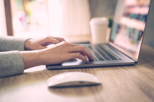A mulher de negócios que usa o laptop faz a atividade on-line no escritório de madeira da tabela em casa.