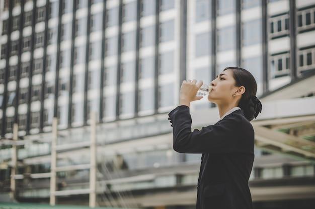 A mulher de negócios toma um resto bebendo água na frente do centro de negócios.