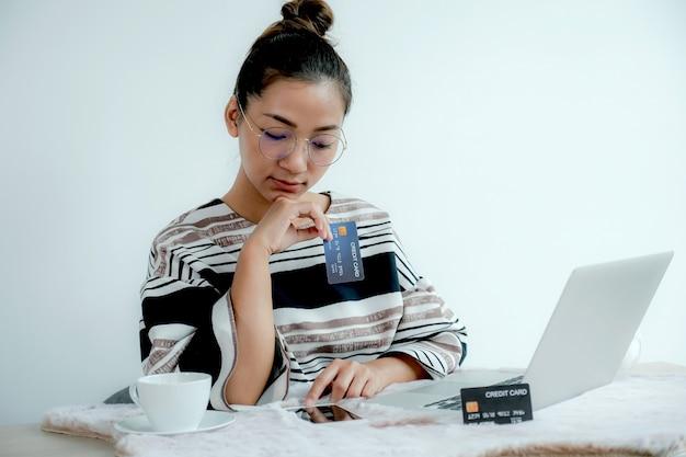 A mulher de negócios usa um cartão de crédito para fazer compras online em casa com um laptop.